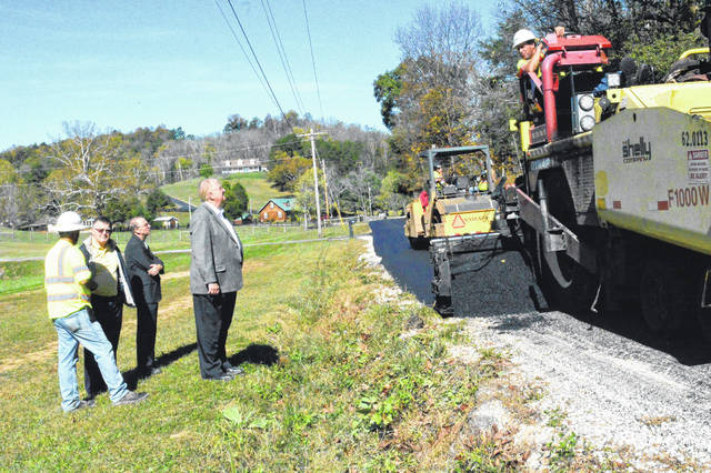 Gallia Commissioners speak with contract workers as they finish laying asphalt during the sewer construction project through Green Township.