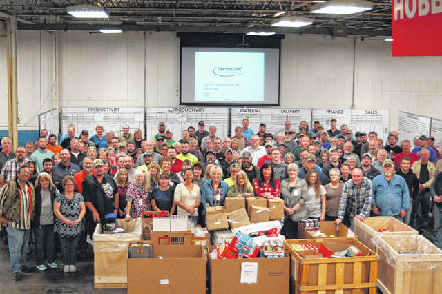 Plant staff surrounds the food gathered, which will be donated in the coming days to multiple local charities.