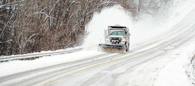 A plowing truck clears the road for area travelers.