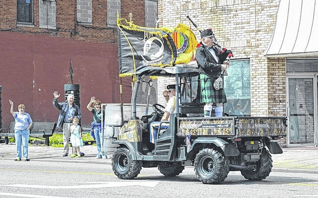 Parade onlookers wave to Gallia County veterans as they pass by on Second Avenue to commemorate the struggles of Vietnam War veterans in a past parade. Gallipolis VFW Post 4464 Commander Bill Mangus salutes onlookers while Chaplain John Jackson rides as a passenger. William Holmes Jr. plays bagpipes in the ATV bed.