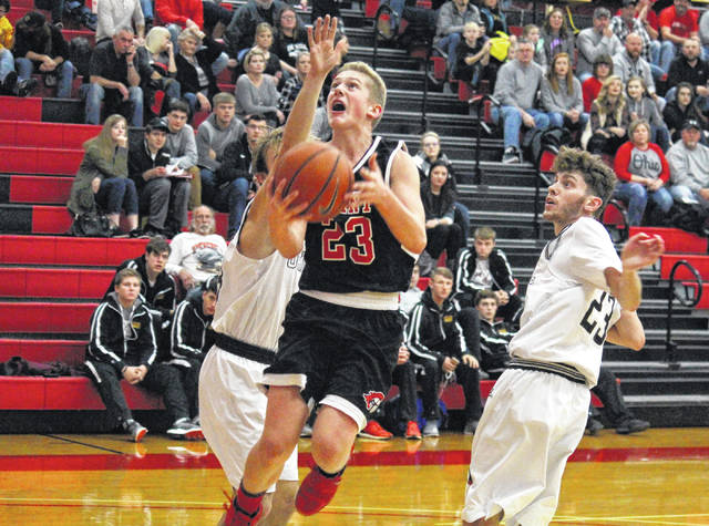 Point Pleasant freshman Hunter Bush (center) splits a pair of Oaks for a layup, during Oak Hill's 78-39 victory on Saturday in Rio Grande, Ohio.