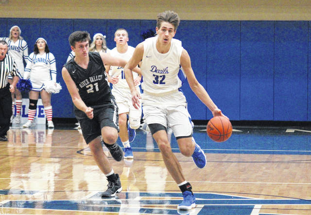 Gallia Academy sophomore Zach Loveday (32) drives past River Valley sophomore Matthew Mollohan (21), during the Blue Devils' 68-28 victory on Friday in Centenary, Ohio.