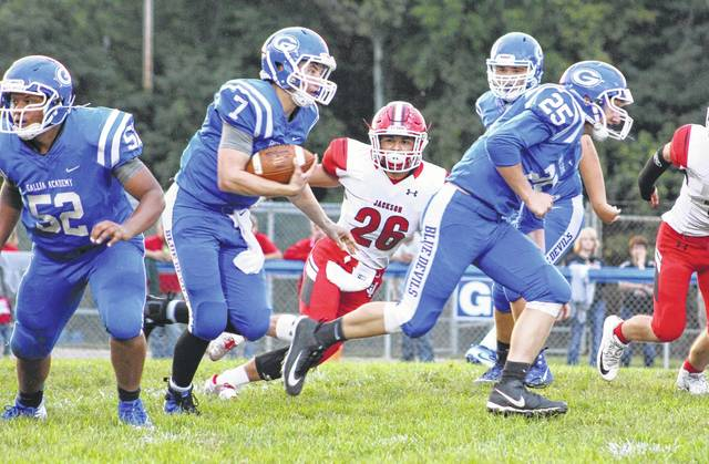 Gallia Academy junior quarterback Justin McClelland (7) follows a block by teammate Caleb Henry during a first quarter run against Jackson in a Week 3 football contest at Memorial Field in Gallipolis, Ohio.