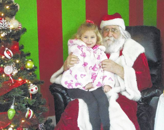 Chester Polcyn sits with one of his young visitors to the Santa House in Gallipolis City Park in December 2015.