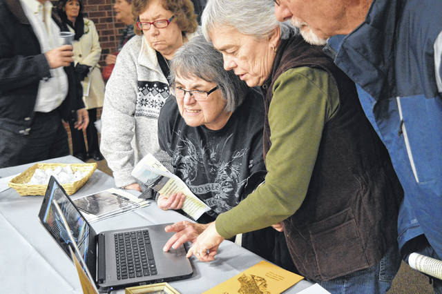 Visitors to the Gallipolis Bossard Library Bridge Memorial event listen to an original recording of a radio news broadcast form the day of the Silver Bridge Collapse.