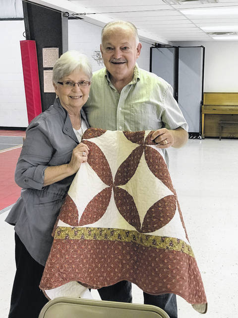 Pat and Henry Dillon are shown with a quilt.