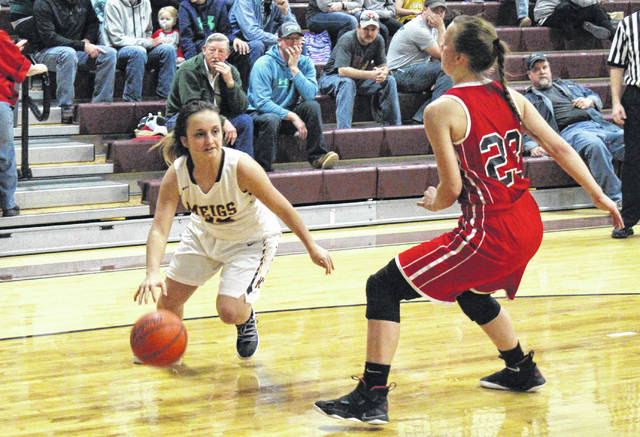 Meigs senior Madison Hendricks (left) drives past Wayne senior Maddie Wilcox (23), during the second half of the Lady Marauders' 57-51 loss on Saturday in Rocksprings, Ohio.