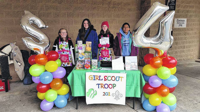 Gallia Girl Scout Troop 201 stands outside a store on a cold day selling cookies.