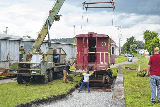 Jim Posey lowers the caboose top onto the waiting trucks.