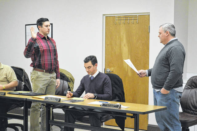 Cody Caldwell, left, is sworn in as a Gallipolis City Commissioner Tuesday evening by City Solicitor Adam Salisbury, right. Beau Sang, center, was also sworn in alongside veteran city commissioner Tony Gallagher, not pictured.