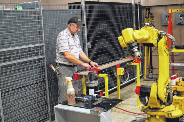 FANUC robotic arms are used as a standard in automated manufacturing. The ARMS program at BHCC has two they have arranged for students to operate and program to move rings about through a process, which start on this conveyor belt with sensors to communicate with the robots.