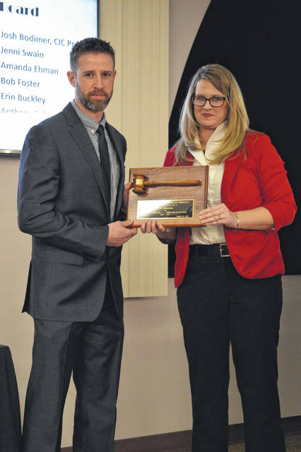 Josh Simmons, left, is recognized for his service as the Chamber's immediate past president with new Chamber President Meagan Matura at right during the Gallia Chamber of Commerce's 81st Awards Ceremony Thursday at Bossard Memorial Library.