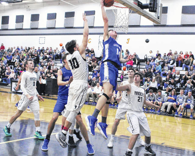 Gallia Academy sophomore Logan Blouir (14) releases a shot attempt in front of River Valley defenders Dustin Barber (10) and Matthew Mollohan (21) during the second half of Tuesday night's non-conference boys basketball contest in Bidwell, Ohio.