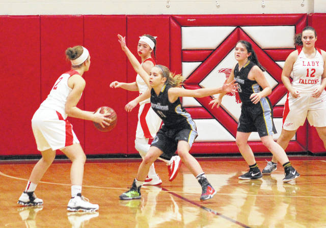 Ohio Valley Christian defender Acacia Peck (11) applies pressure to a Wahama player during the second half of Thursday night's girls basketball contest at Gary Clark Court in Mason, W.Va.