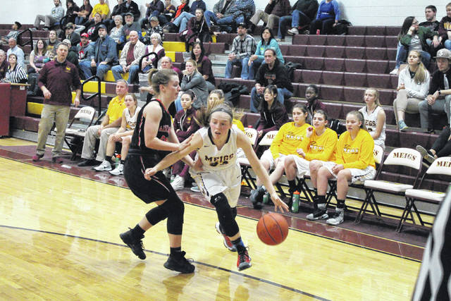 Meigs junior Becca Pullins (right) drives past Alexander sophomore Mallory Rankin (left), during the fourth quarter of the Lady Spartans' 49-36 victory on Thursday in Rocksprings, Ohio.