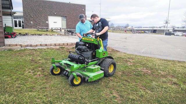Instructor Kyle Deel (left) teaches a Building and Grounds Maintenance student Shae Beaty (right) how to operate a stand on lawn mower.