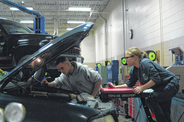 Two students work to diagnose an electrical problem under the hood a Ford truck.