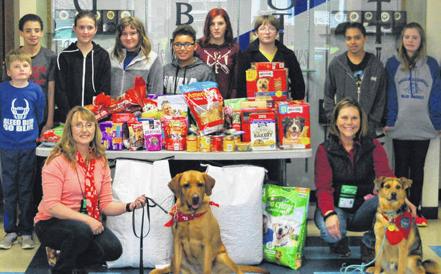 Students collected food and treats and funds to donate to the Gallia County Canine Shelter. Several middle school students pose here with Ginger and Tate, two therapy dogs on hand for the schools puppy day.