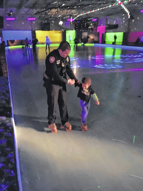 Officer Gary Waldron helps teach a young boy how to skate.