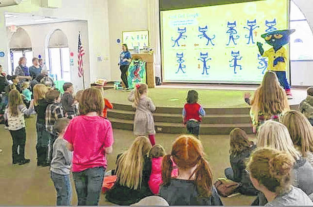 Pete the Cat is pictured on stage as he leads children in the Pete the Cat Boogie Dance. Rachael Barker, youth services programming coordinator, is pictured as well.