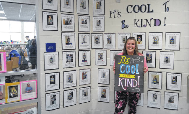 "Felicity Matthew was recently chosen for the ""Cool to be Kind"" award at Gallia Academy High School, a special recognition for doing something kind to others. Behind her on the wall are pictures of all the other students to have been recognized for being kind."