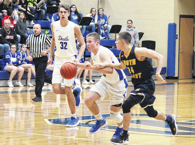 GAHS junior Justin McClelland (center) drives between teammate Zach Loveday (32) and South Point's Tayshaun Fox (24), during the Blue Devils' win over the Pointers on Feb. 2 in Centenary, Ohio.