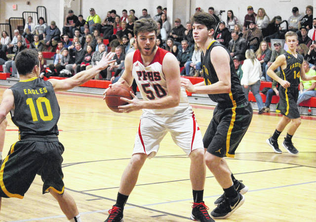 PPHS senior Trace Derenberger (50) drives between Eagles Sharp Facemyer (10) and Kaleb Hill during a non-conference game on Jan. 23 in Point Pleasant, W.Va.