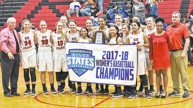 Members of the University of Rio Grande women's basketball team hold up the program's newest banner after capturing the 2017-18 River States Conference tournament championship on Tuesday night at Newt Oliver Arena in Rio Grande, Ohio.