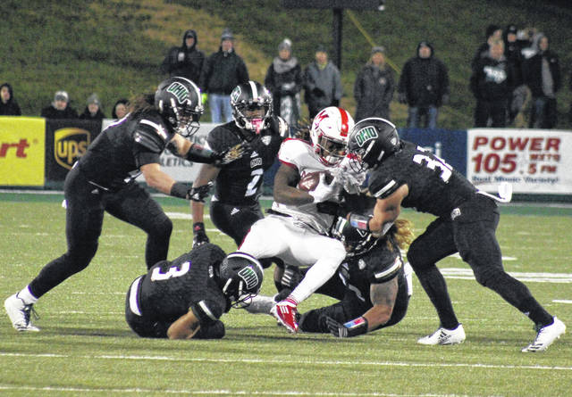 Members of the Ohio defense swarm a Miami ball carrier during a MAC game on Oct. 31, 2017, in Athens, Ohio.