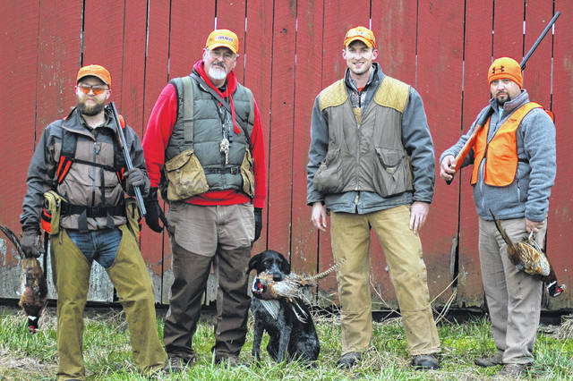 From left are Braeden Windham, Steve Kane, Nick Shale, and Wes Corbin with Lizzy the dog and their harvest for the morning.