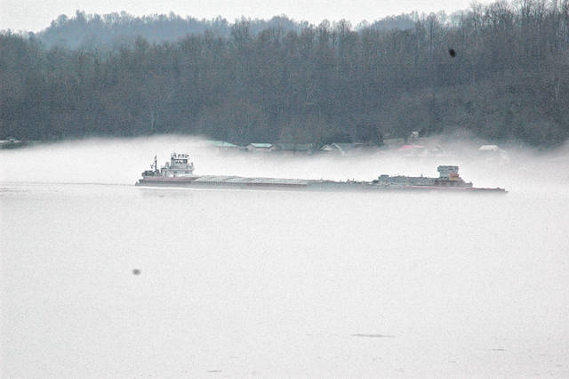 A chemical barge works it way up river in the midst of thick fog on the Ohio River Thursday morning.