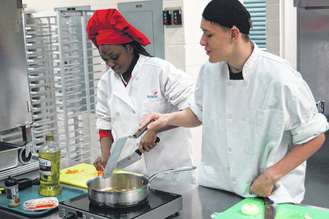 Tyra Nickson, left, and Gary Hammon prepare a special dish during lab time in Culinary Prep.
