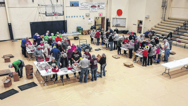 Volunteers gather in the Ohio Valley Christian School gym to prepare food for Haiti citizens in need.
