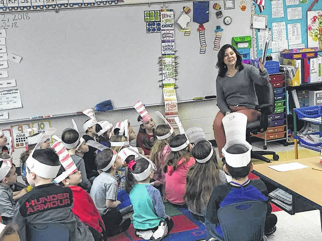 Principal Julie Bays reads to students with Cat in the Hat themed hats for Read Across America Day, celebrating Dr. Seuss' birthday and promoting literacy in schools.
