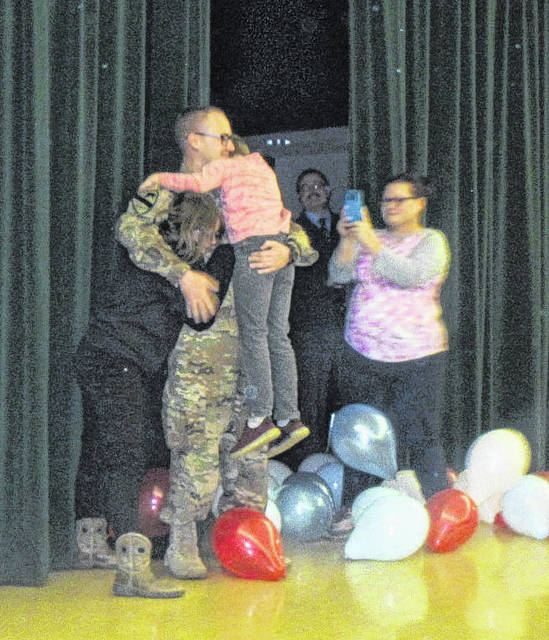 Army National Guard Specialist Jacob Roach hugs his siblings on Monday after surprising them at school.