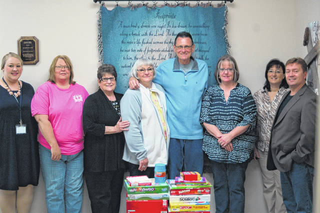 From left are Cassie Walker, Laura Lewis, Judy Jones, Sandra Dennis, Kevin Dennis, Becca Loscar, Marlene Stout, and Pastor Ray Kane. Loscar, Kane, and Stout are from Grace United Methodist Church and helped donate games to the Hope House.