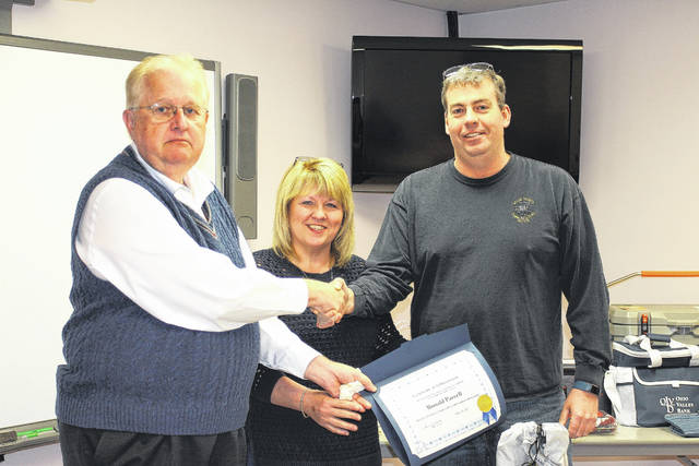 Gallia Commissioner Harold Montgomery, left, and Gallia EMA and 911 Center Director Sherry Daines, center, recognize Ron Parcell, right, as Gallia County's 911 Dispatcher of the Year.