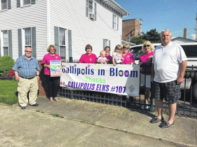 From left to right stand Tony Gallagher, Bev Dunkle, Diana Parks, Erica Preston, Katie Preston, Brooke Preston, Kim Canaday, Cindy Staley, Elks ER David Swain. Gallipolis in Bloom recently the Gallipolis Elks have been one of its biggest supporters and recently gifted them with a banner for the Elks' continued support GIB's beautification project.