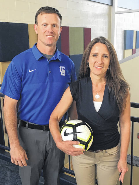 Gallia Academy High School athletic director Adam Clark, left, joins GAHS girls varsity soccer coach Leah Polcyn for a photo as the Blue Angels open varsity soccer for the first time in school history during the 2018-19 school year.