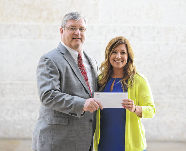 Tim Wells, manager of economic and business development for AEP Ohio, left, presents a grant check to Gallia Economic Development Director Melissa Clark in 2016.