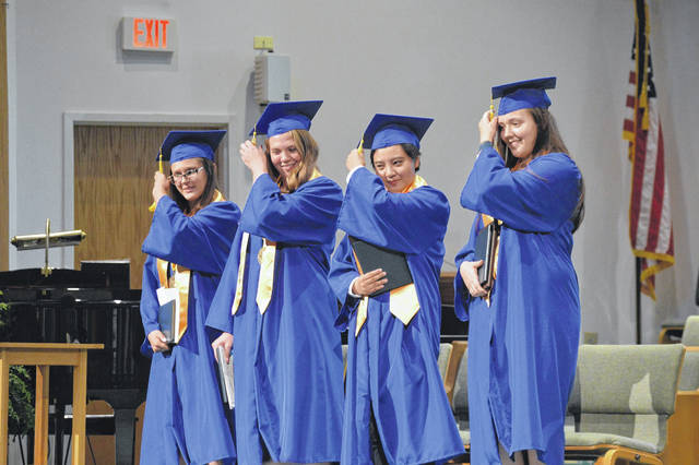Shelby Bing, Cori Hutchison, Yu Yan Sun and Katie Westfall move their tassels as a signal of their graduation from Ohio Valley Christian School on Saturday.