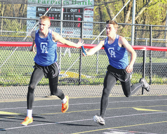 The Gallia Academy duo of Spencer Harris, left, and Coen Duncan complete a baton exchange during the 4x200m relay event on Monday night at the 2018 Battle for the Anchor at Ohio Valley Bank Track and Field in Point Pleasant, W.Va.