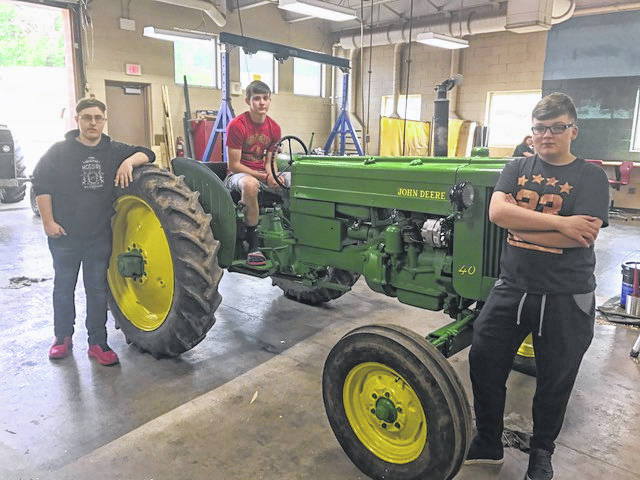 Students in the Mechanical Principles class at South Gallia HS spent this term working on a 1953 John Deere tractor. The tractor was completely reconditioned by the students including converting to 12 volt electronic ignition and a new paint job. Pictured are Kyle Northup (owner) sitting on tractor with classmates Zach McGuire and Shawn Ward. The Mechanical Principles class is offered through the Vocational Agriculture program at South Gallia under the instruction of Dave Pope.