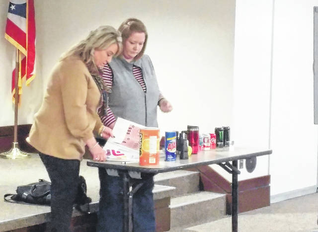 Lisa Osborne, left, and Selina Mitchell, right, display various items donated to Gallia Citizens for Prevention and recovery to display how drugs may be hidden at a previous meeting.