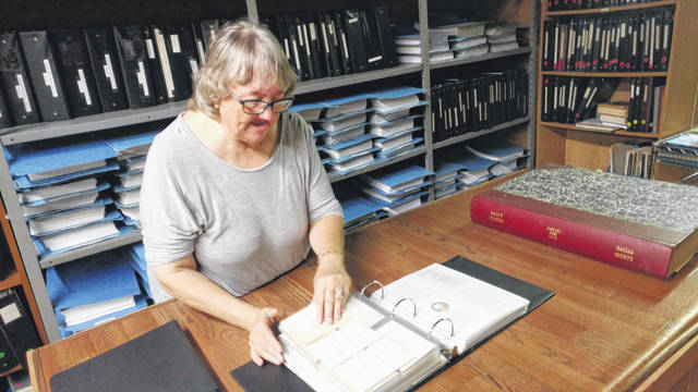 Co-chair of the Gallia Historical Society Cheryl Enyart searches though text at the society on Second Avenue.