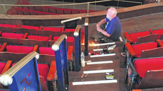 Professor of Art Kevin Lyles at the University of Rio Grande inspects handrails placed in the balcony of the Ariel Opera House. He and Dylan Collins of West Virginia University spent last week installing and painting the new rails in keeping with the performance center's aesthetic.