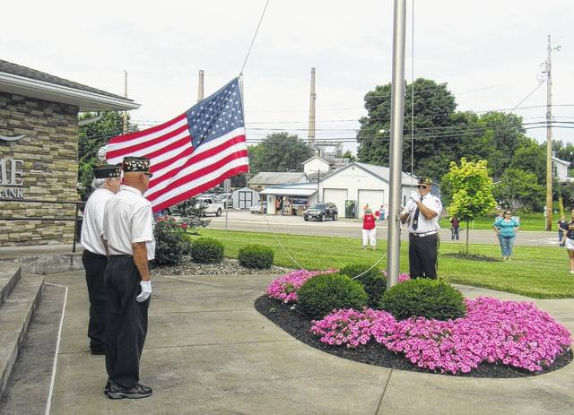 American Legion Post 602 in Racine conducts a flag raising in front of Home National Bank as part of the Fourth of July parade in Racine.