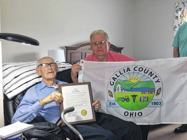 Mason Maynard, left, sits with Gallia Commissioner Harold Montgomery, Thursday, in recognition of Maynard's 100th birthday. Maynard was presented with plaque to celebrate his longevity and a Gallia flag.