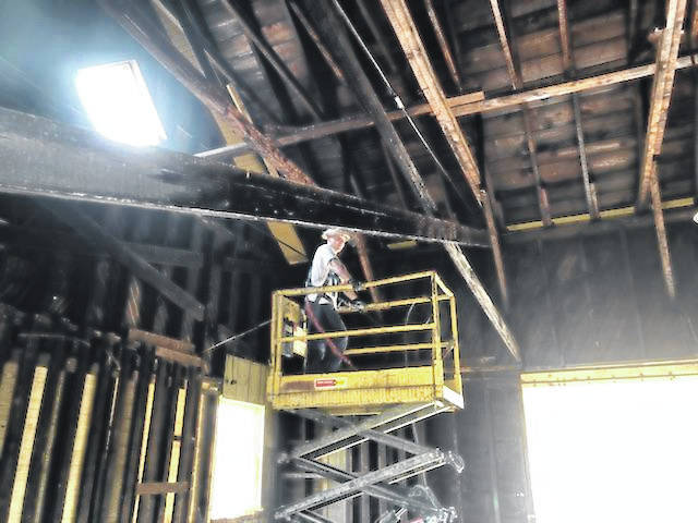 Workers inspect the rafters of the Gallipolis Railroad Freight Station Museum during cleaning to remove bird excrement.