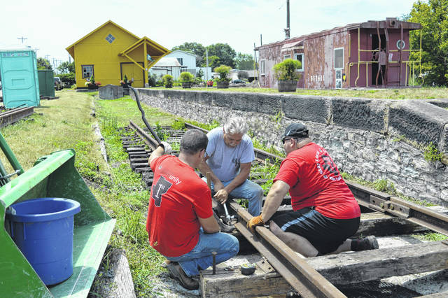 Volunteers from Ohio Valley Bank connect rails for the Gallipolis Railroad Freight Station Museum, Thursday afternoon. The museum is laying more track in anticipation of the addition of a passenger car and a locomotive engine to complement its caboose. Museum board members are already searching to rehabilitate the caboose alongside the original freight station building.